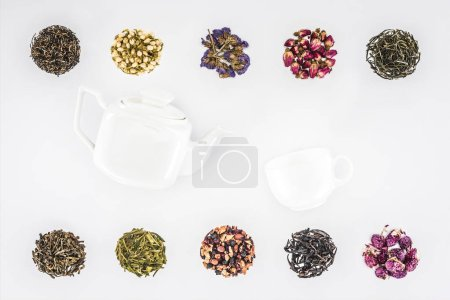 top view of dried herbal organic tea and teapot with cup isolated on white