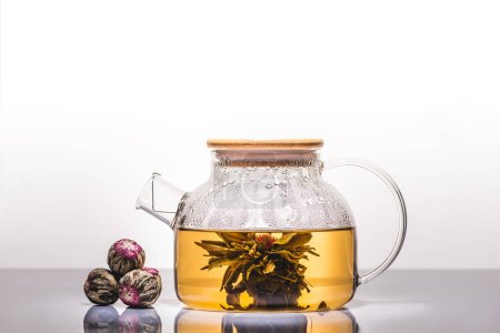 glass teapot of chinese flowering tea with tea balls on table