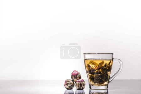 Photo for Cup of chinese flowering tea with tea balls on table - Royalty Free Image