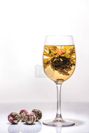 Foto de Hermoso vaso de té chino flores con bolas de té en la mesa - Imagen libre de derechos