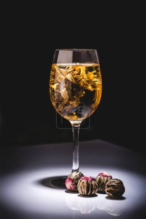 Foto de Vaso de té tradicional chino flores con bolas de té sobre mesa aislado en negro - Imagen libre de derechos