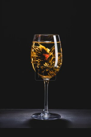 glass of chinese flowering tea on table isolated on black