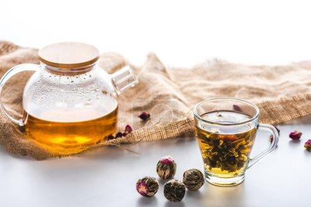 tasse de thé chinois floraison, théière, chiffon et boules à thé sur la table