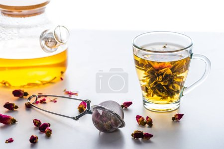 cup of chinese flowering tea, teapot and tea strainer with dried rose buds