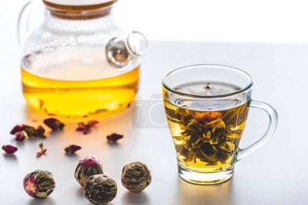 Foto de Taza de té chino de flores con bolas de té sobre la mesa blanca - Imagen libre de derechos