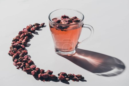 dried rose buds tea in cup and reflecting shadow on white tabletop