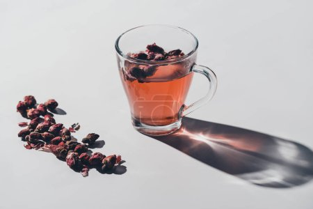 red tea of dried roses in cup on white tabletop