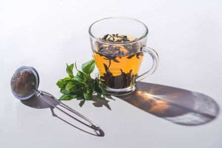 cup of black tea, mint and tea strainer on white tabletop