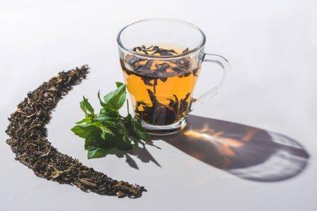 tasse de thé noir et à la menthe sur le dessus de table blanc