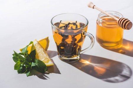 bonne santé thé noir au miel, citron et menthe dans la tasse sur la table blanche