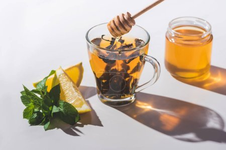 healthy tea with honey, lemon and mint on white tabletop