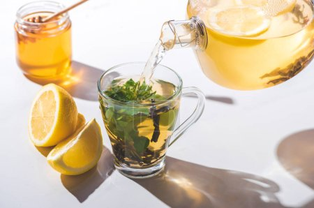 pouring healthy tea with lemon and mint from teapot into cup on white tabletop