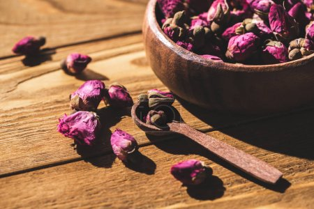 dried rose buds in wooden bowl and spoon on wooden table
