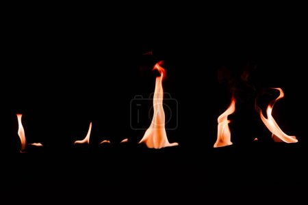close up view of small burning orange fire on black backdrop