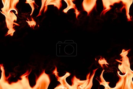 close up view of burning orange flame with blank space in middle on black background
