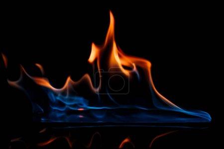Foto de Vista de cerca de la llama naranja y azul ardiente sobre fondo negro - Imagen libre de derechos