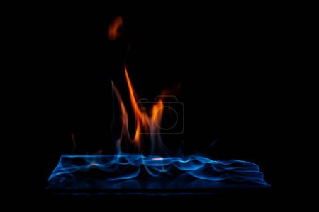 close up view of burning orange and blue flame on black background