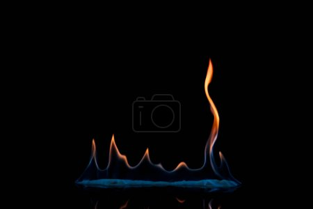 close up view of small burning orange and blue flame on black background