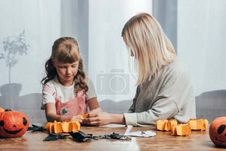 Photo for Young woman and little sister handcrafting paper figures for halloween together at home - Royalty Free Image