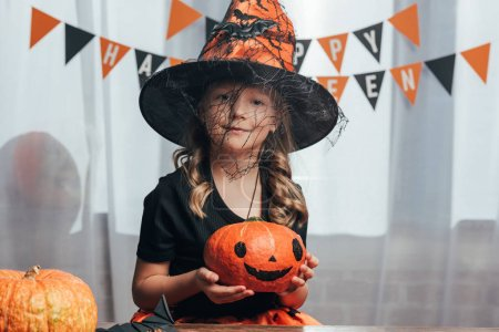 portrait of adorable child in witch halloween costume holding pumpkin at home