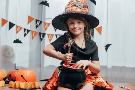 portrait of smiling child in witch halloween costume with black pot full of candies at home