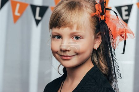 portrait of adorable smiling kid looking at camera wit halloween flags hanging behind at home