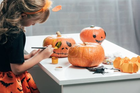 side view of cute child painting pumpkins for halloween at home