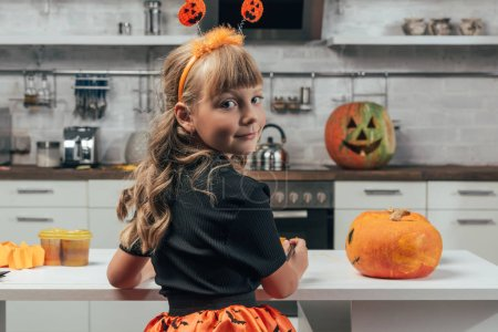 back view of kid in halloween costume at tabletop with pumpkins in kitchen at home