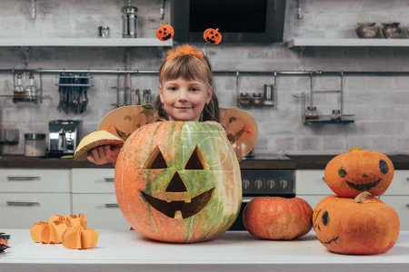portrait of smiling kid in halloween costume standing at big carved pumpkin on tabletop in kitchen at home