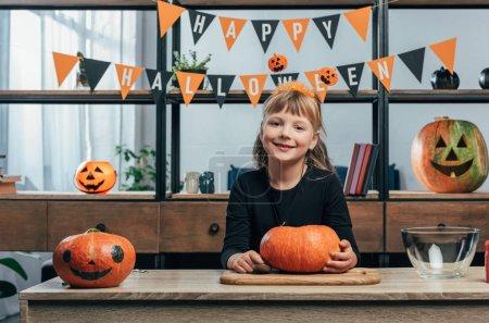 Photo pour Portrait d'un enfant souriant sur la table avec des citrouilles et accrochant des drapeaux d'Halloween heureux derrière chez lui - image libre de droit