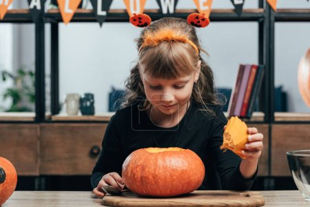 portrait of adorable child at tabletop with pumpkin for halloween at home