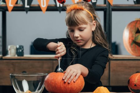 Photo for Portrait of little child carving pumpkin for halloween alone at tabletop at home - Royalty Free Image