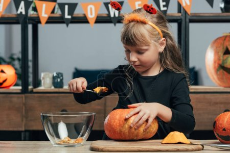 portrait of cute kid carving pumpkin for halloween alone at tabletop at home