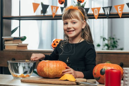 portrait of smiling kid looking at camera while carving pumpkin for halloween alone at tabletop at home