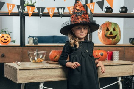 portrait of adorable kid in witch halloween costume leaning on wooden tabletop at home