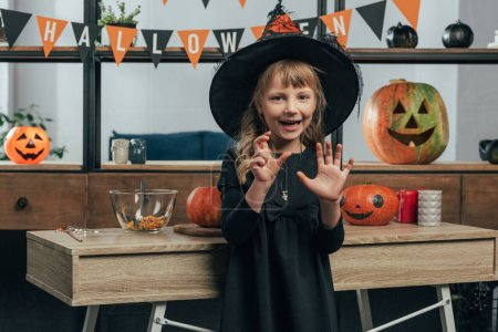 portrait of adorable kid in witch halloween costume gesturing at home