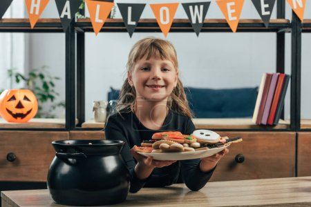 portrait of smiling child showing plate with halloween cookies at home