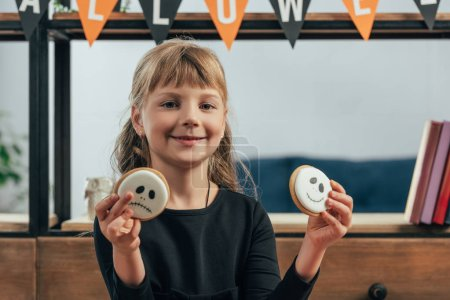 portrait of smiling child showing halloween cookies in hands at home