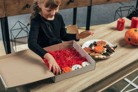 adorable kid arranging themed halloween cookies at wooden tabletop at home