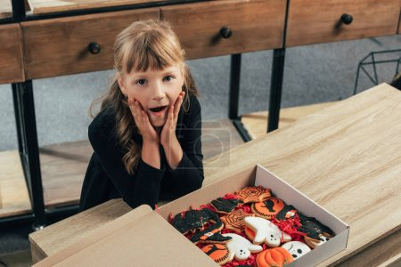 high angle view of shocked kid looking at camera at tabletop with halloween cookies in box at home