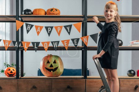 cute kid on ladder hanging flags with happy halloween inscription at home