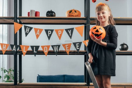 adorable kid with pumpkin standing on ladder at hanging flags with happy halloween inscription at home