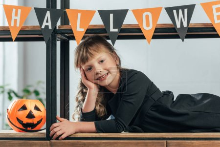 portrait of smiling kid looking at camera in decorated room for halloween