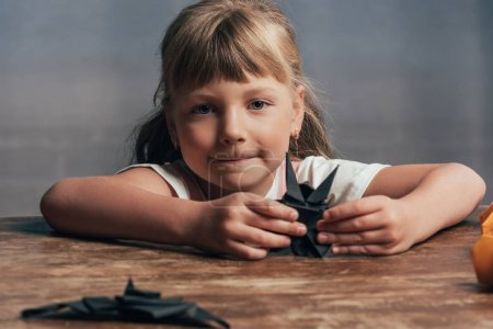 portrait of little child with black paper bats looking at camera at home