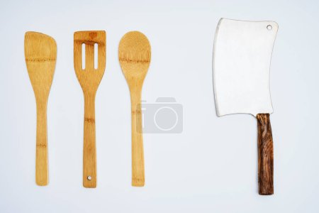 top view of wooden kitchen utensils and meat cleaver isolated on grey