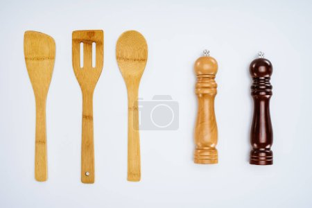 top view of wooden kitchen utensils and spice containers isolated on grey