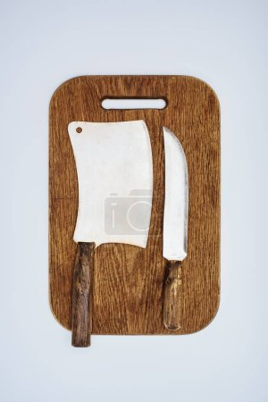 top view of kitchen knife and cleaver on wooden cutting board isolated on grey