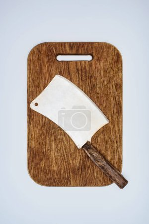 top view of meat cleaver on wooden cutting board isolated on grey