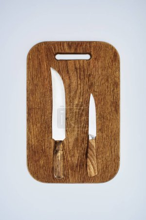top view of two kitchen knives on wooden cutting board isolated on grey