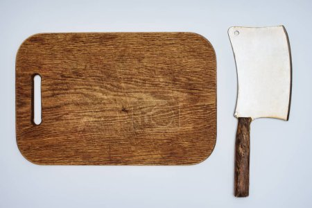 top view of wooden chopping board and meat knife isolated on grey